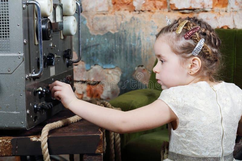 Mała śliczna dziewczyna konfiguruje źródło zasilania radiowy odbiorca fotografia stock