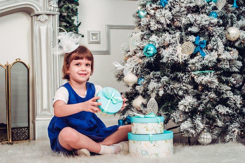 Mała śliczna dziewczyna otwiera prezenty pod choinką obrazy stock