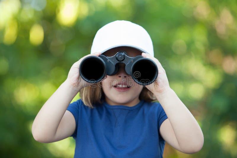 Mała śliczna dziewczyna patrzeje lornetkami w parku zdjęcia stock