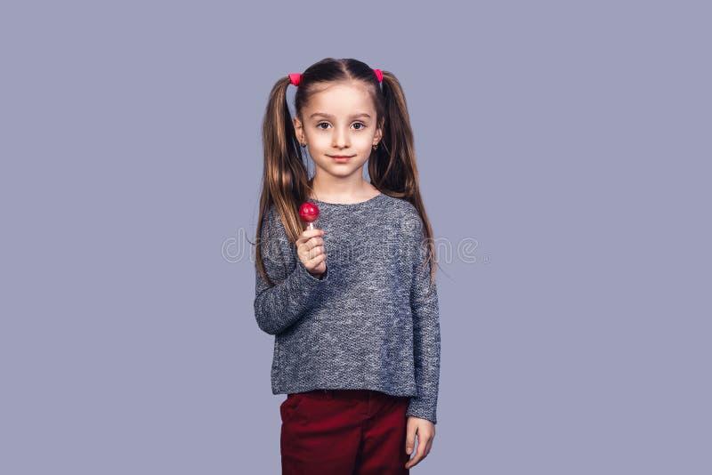 Mała śliczna dziewczyna trzyma czerwonego lizaka fotografia royalty free