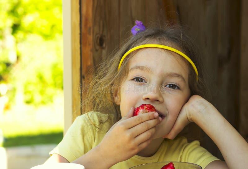 Mała śliczna dziewczyna trzyma truskawki w letnim dniu fotografia stock