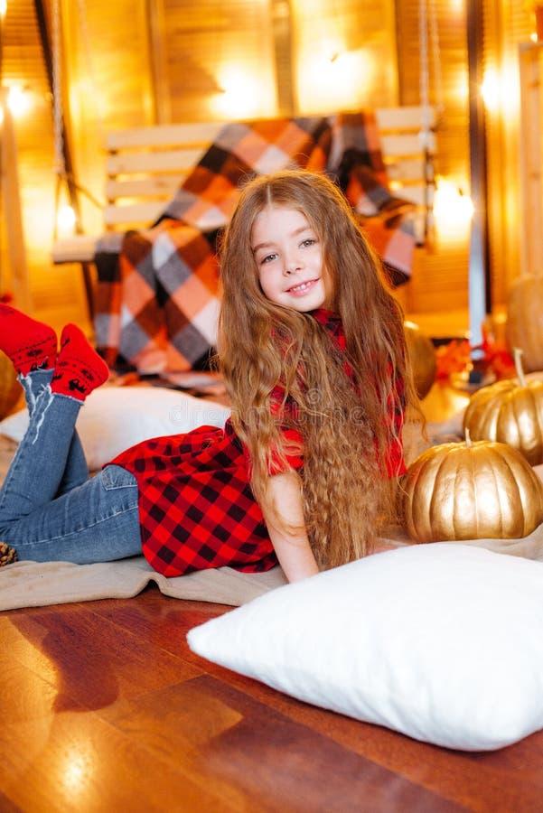 Mała śliczna dziewczyna z długim kędzierzawym włosy blisko bani w czerwonej w kratkę koszula i huśtawki obrazy stock
