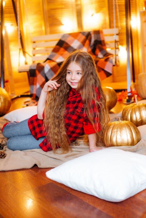 Mała śliczna dziewczyna z długim kędzierzawym włosy blisko bani w czerwonej w kratkę koszula i huśtawki fotografia stock