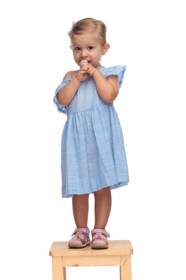 Mała śliczna dziewczynka jest beig okaleczającym i patrzeje niespokojną obrazy royalty free