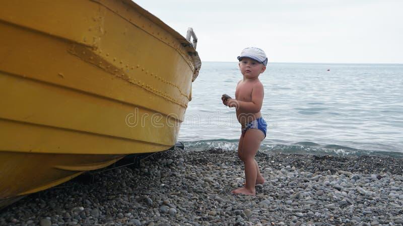 Mała śliczna urocza chłopiec stoi na dennym brzeg blisko łodzi obrazy royalty free