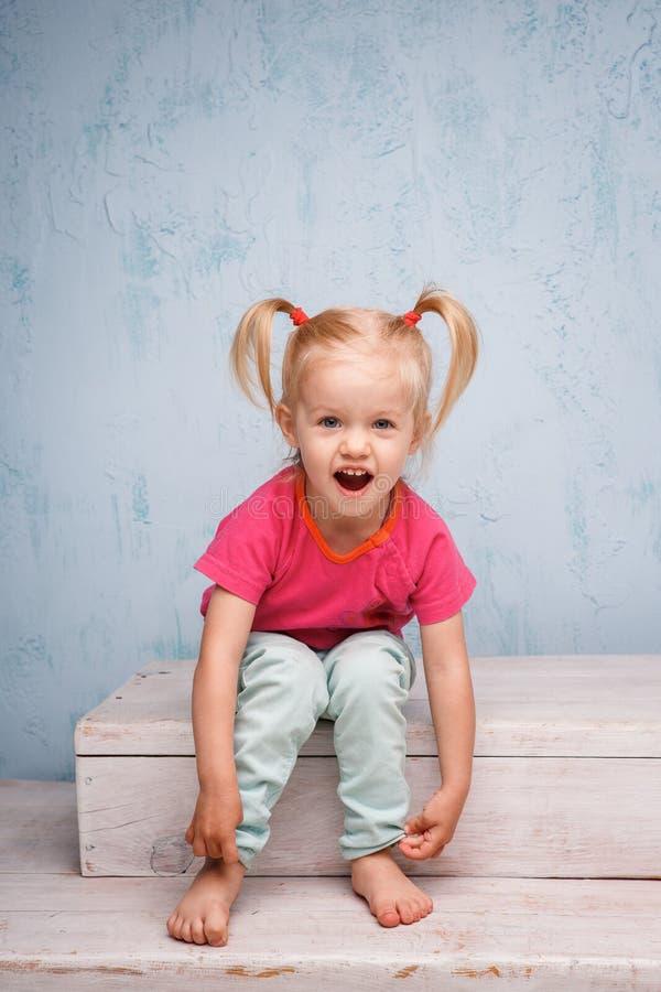 Mała śmieszna błękitnooka dziewczyny dziecka blondynka z ostrzyżenia dwa ponytails na ona kierowniczy obsiadanie na plotce na tle zdjęcia royalty free