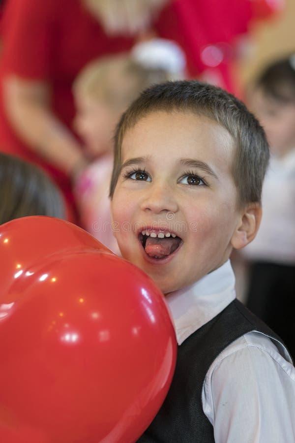 Mała śmieszna chłopiec z czerwień balonem portret śmieszny dzieciak trzyma dużego czerwień balon przeciw abstrakcjonistycznemu tł zdjęcie royalty free
