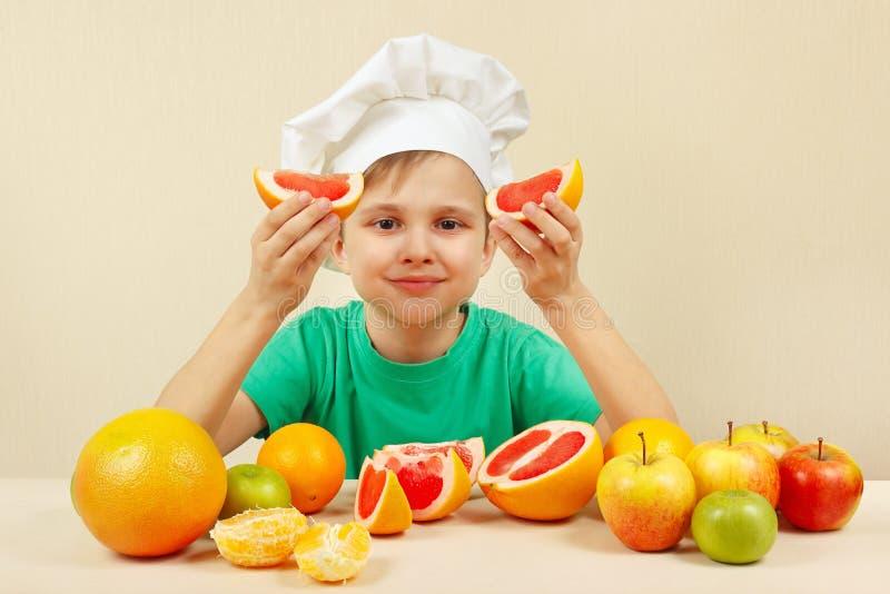 Mała śmieszna chłopiec z dwa plasterkami grapefruitowy przy stołem z owoc zdjęcia royalty free
