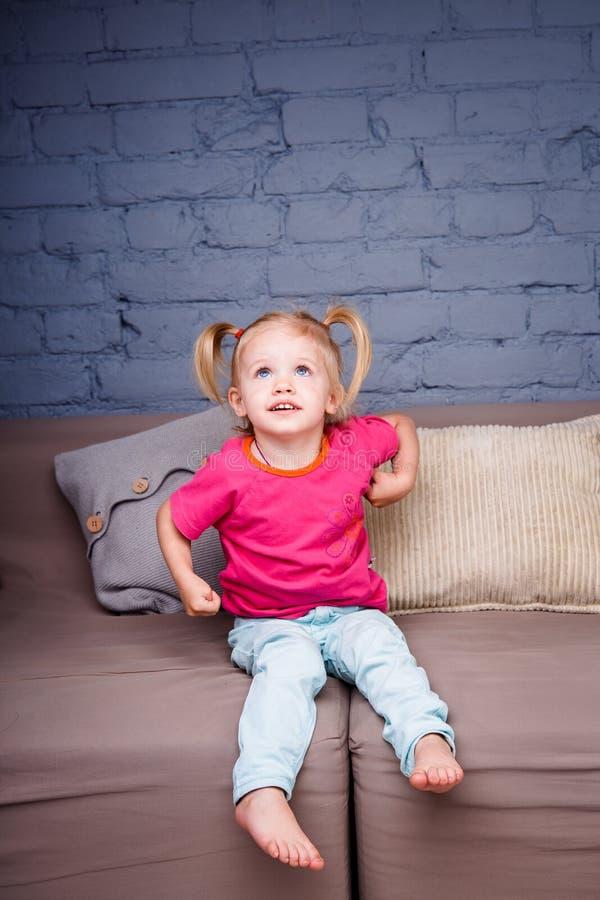 Mała Śmieszna dziewczyna Pampering W Domu i Bawić się Na kanapie Pokazuje Nagie pięty Śmia się pokazywać jego zęby i jęzor Jest d obraz stock