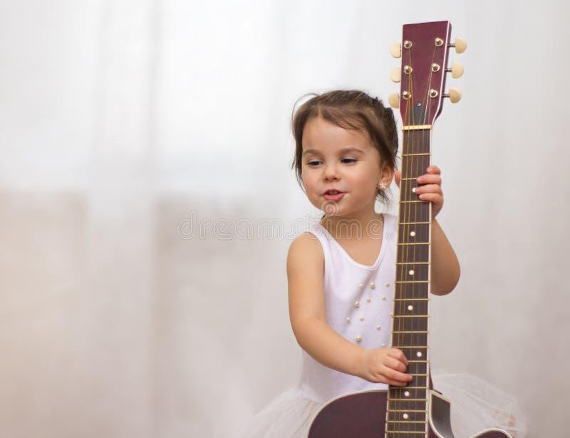 mała śmieszna uśmiechnięta dziewczyna w płatek śniegu kostiumu z gitarą akustyczną w musical szkole obrazy stock