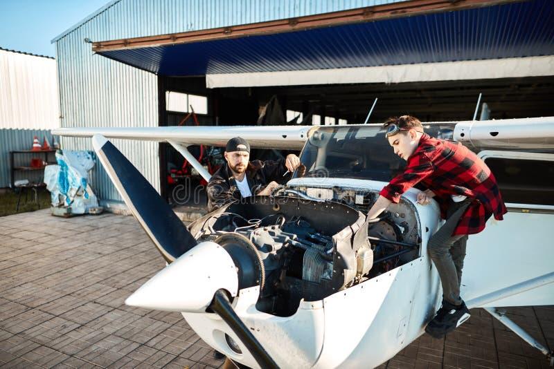 Mała śmigła powietrza strumienia pozycja na zewnątrz hangaru, pilota i jego syna sprawdza silnika, obraz royalty free