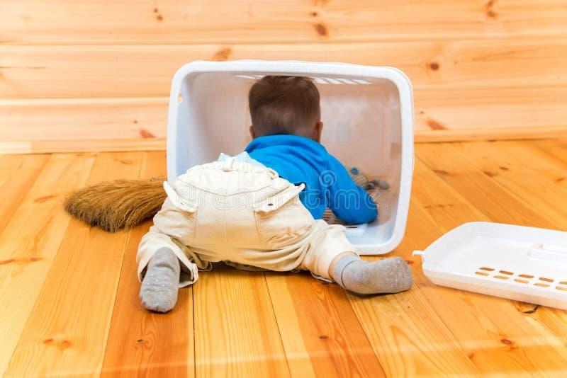 Mała aktywna chłopiec pomaga czyścić dom dostaje inside kosz zdjęcia royalty free