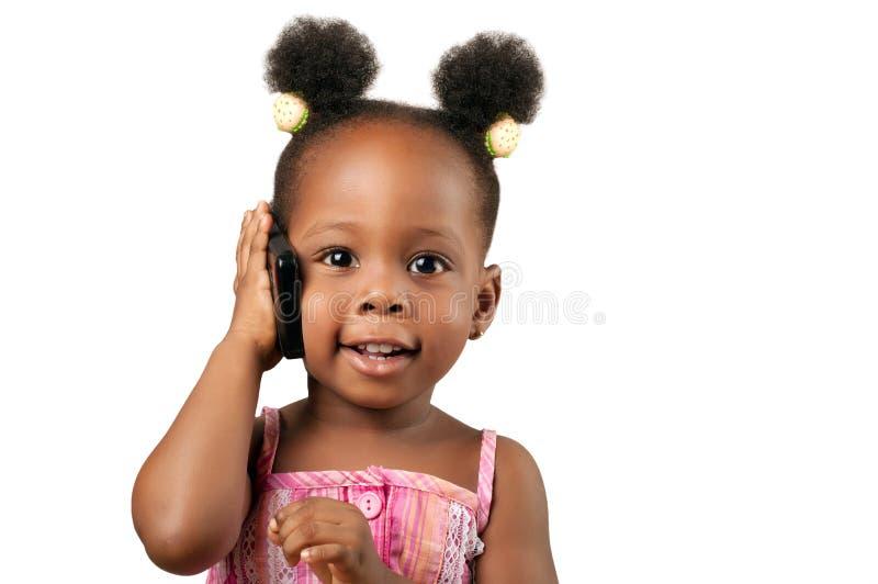 Mała amerykanin afrykańskiego pochodzenia dziewczyna opowiada telefon obrazy royalty free