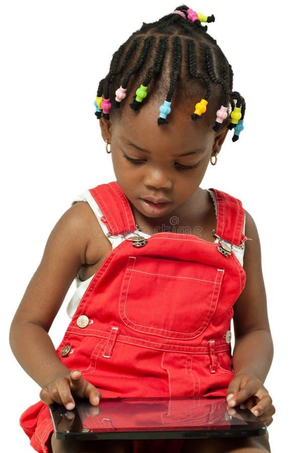 Mała amerykanin afrykańskiego pochodzenia dziewczyna używa pastylka komputer osobistego zdjęcie stock