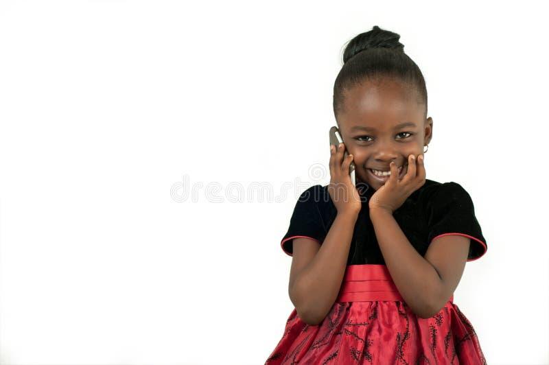 Mała amerykanin afrykańskiego pochodzenia dziewczyna używa telefon komórkowego obrazy stock