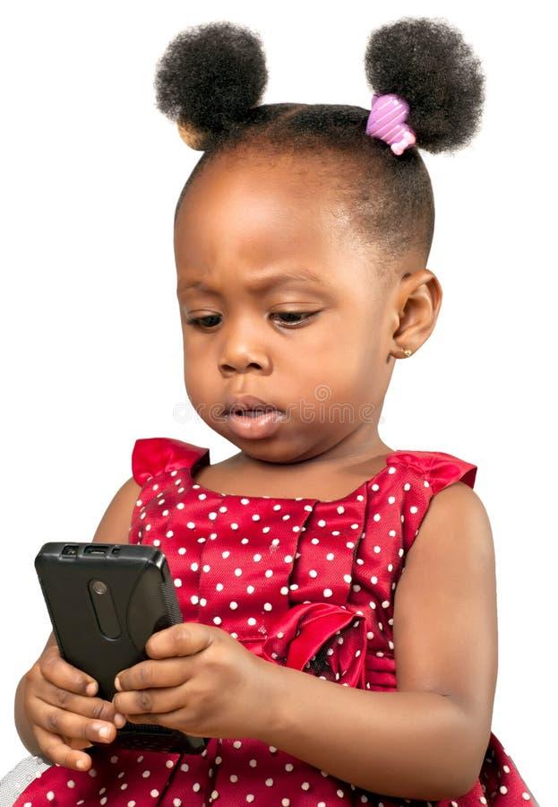 Mała amerykanin afrykańskiego pochodzenia dziewczyna z telefonem komórkowym obrazy royalty free