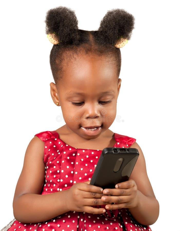 Mała amerykanin afrykańskiego pochodzenia dziewczyna z telefonem komórkowym obrazy stock
