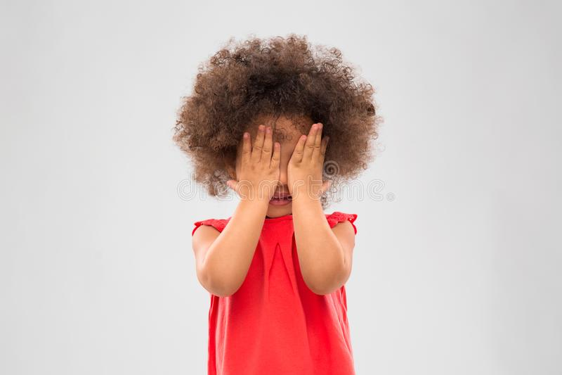 Mała amerykanin afrykańskiego pochodzenia dziewczyna zamyka ona oczy obrazy stock