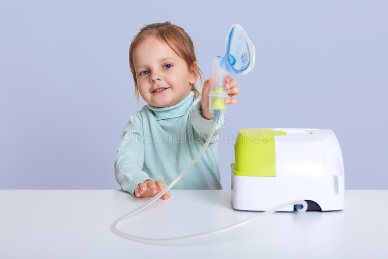 Mała atrakcyjna dziewczyna pokazuje inhalator, robi inhalacji z nebulize, siedzi przy białym biurkiem, taktuje chorobę, ubierając fotografia stock