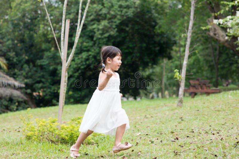 Mała Azjatycka dziewczyna biega outdoors obraz royalty free