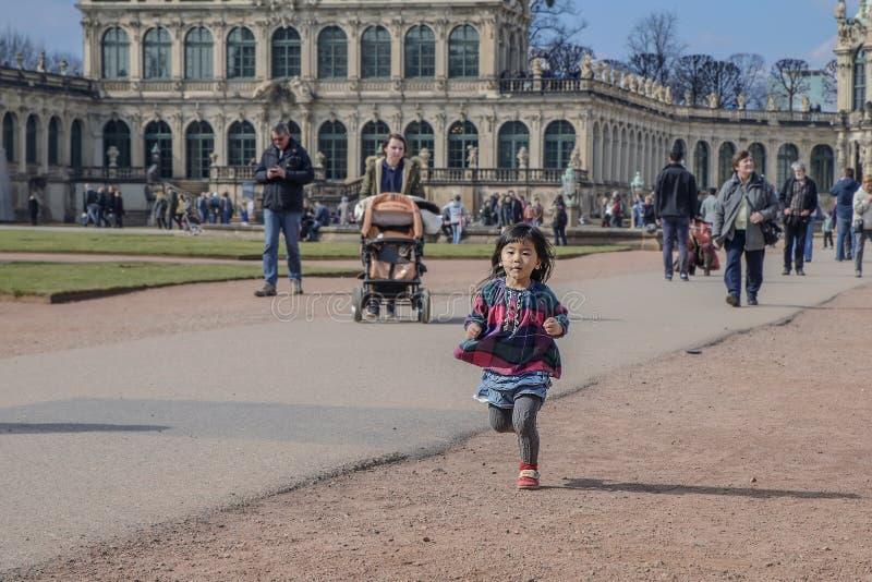 Mała Azjatycka dziewczyna biega wzdłuż ścieżki w Drezdeńskim Zwinger, niemiec obraz royalty free