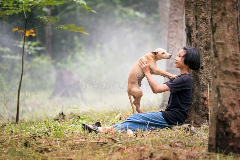 Mała Azjatycka dziewczyna siedzi samotnie na zieleni polu pod drzewem z jej psem, plenerowym przy wsią Tajlandia obrazy royalty free