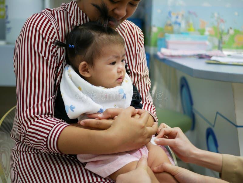 Mała Azjatycka dziewczynka, jeden roczniak, patrzeje pediatryczne pielęgniarki zabezpiecza jej nogę i czyści, przygotowywa dla sz obraz stock