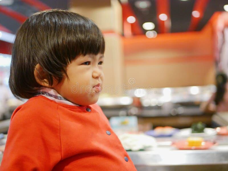 Mała Azjatycka dziewczynka, 25 miesięcy starych, cieszy się łasowania jedzenie, mieć posiłek w restauracji/ obrazy royalty free