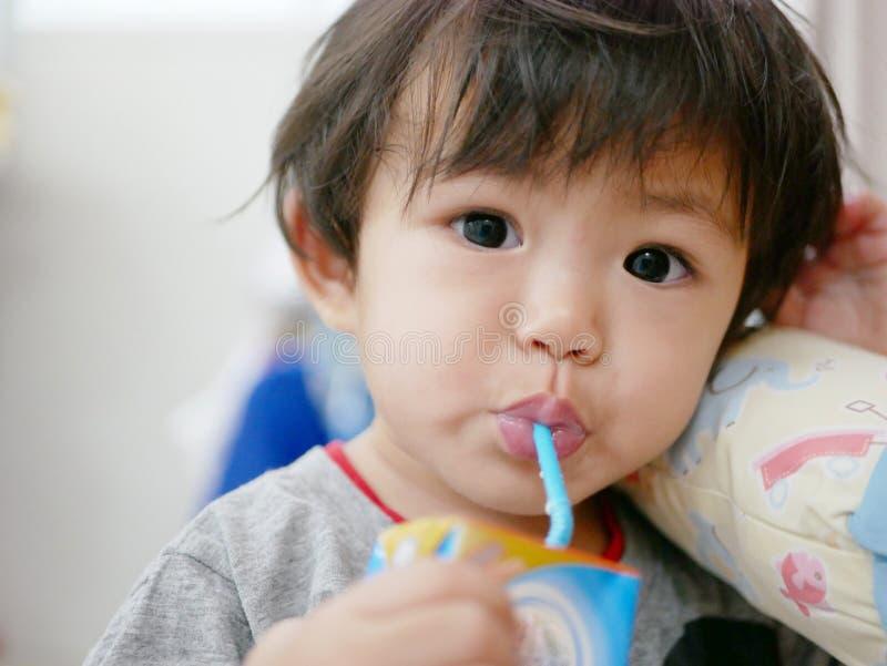 Mała Azjatycka dziewczynka pije mleko od dojnego kartonu ona obrazy royalty free
