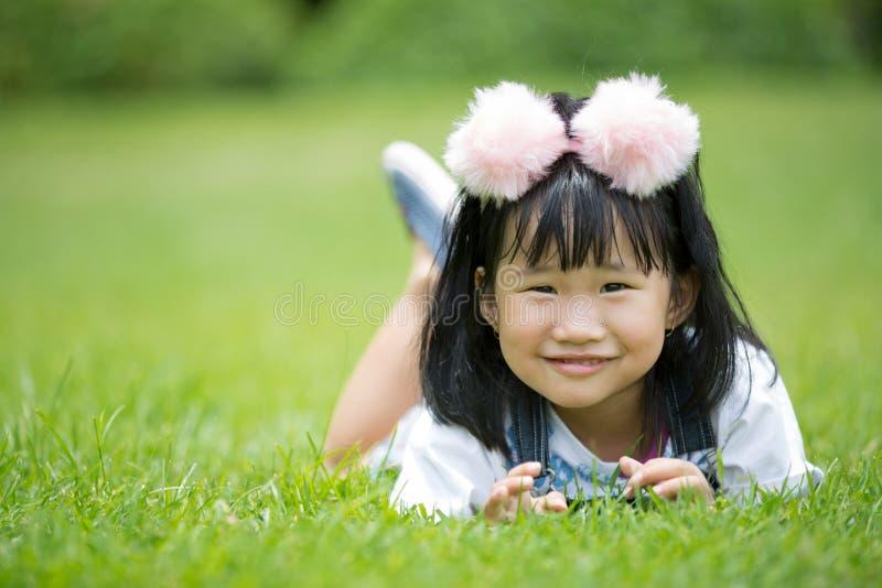 Download Mała Azjatykcia Dziewczyna Bawić Się Na Zielonej Trawie Przy Parkiem Obraz Stock - Obraz złożonej z hairball, bąbel: 57650083