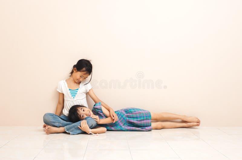 Mała azjatykcia dziewczyna kłaść na jej starej siostrze w domu uroczy powiązanie między rodzeństwami fotografia royalty free