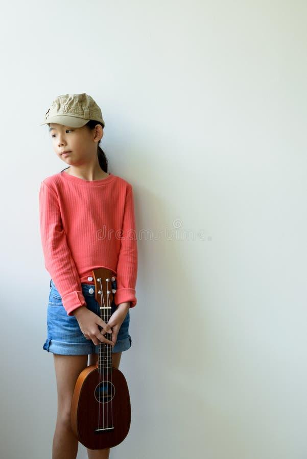 Mała azjatykcia dziewczyna z ukulele obraz royalty free