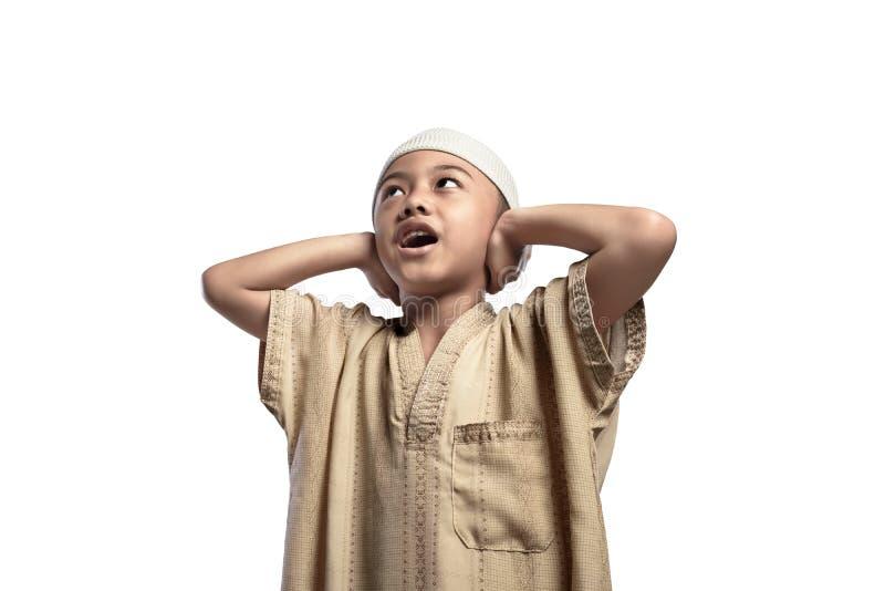Mała azjatykcia muzułmańska chłopiec w tradycyjnym smokingowym modleniu obraz royalty free