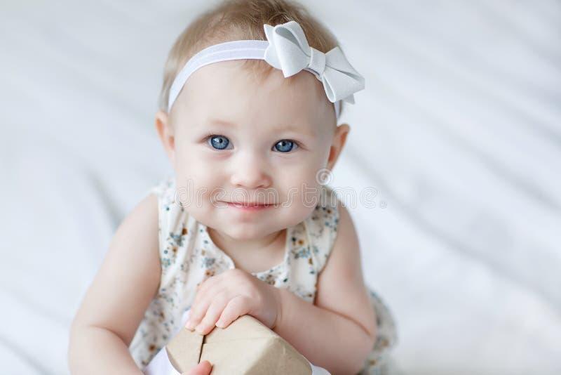 Mała błękitnooka dziewczyna czołgać się na białej przesłonie przeciw tłu choinka fotografia royalty free
