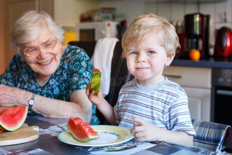 Mała berbeć chłopiec a i jego prababci łasowania arbuz obrazy stock