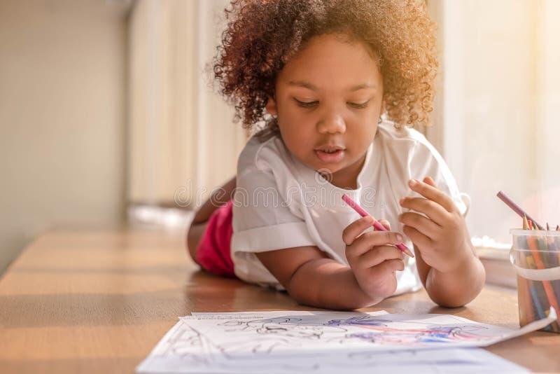 Mała berbeć dziewczyna kłaść w dół koncentrat na rysunku Mieszanki Afrykańska dziewczyna uczy się i bawić się w przedszkolnej kla zdjęcia stock
