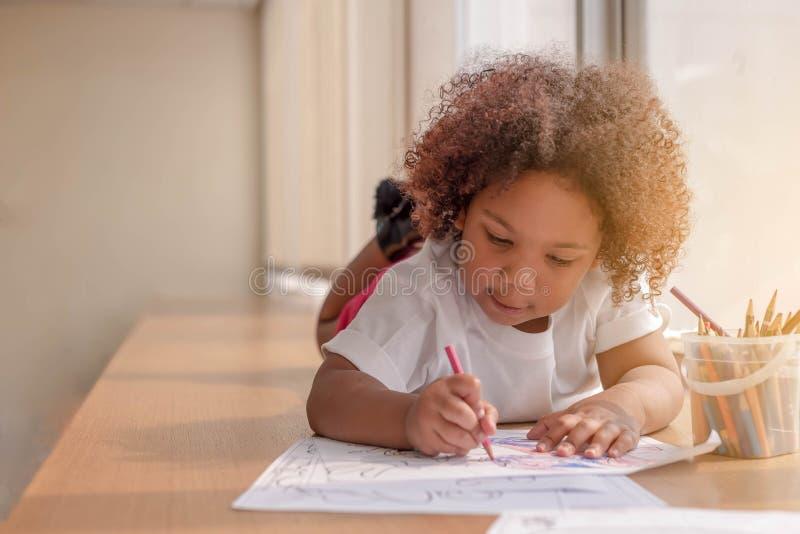 Mała berbeć dziewczyna kłaść w dół koncentrat na rysunku Mieszanki Afrykańska dziewczyna uczy się i bawić się w przedszkolnej kla zdjęcia royalty free