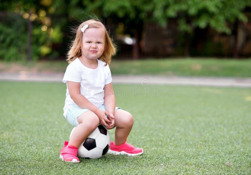 Mała berbeć dziewczyna siedzi na piłki nożnej piłce w zielonym boisku piłkarskim outdoors z śmiesznym w sportach munduruje sneake zdjęcia royalty free