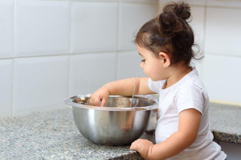 Ma?a berbe? dziewczyna ugniata ciasto w kuchni obrazy stock