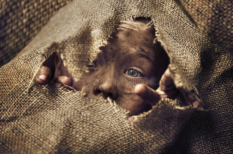 Mała bezdomna chłopiec jest ubranym torbę obrazy stock