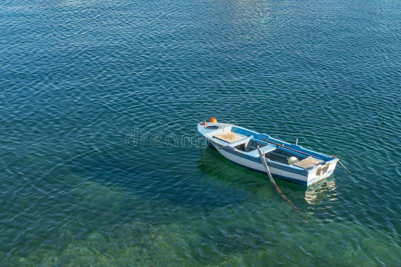 Mała biała błękitna łódź z paddles zakotwiczał na brzeg obraz stock