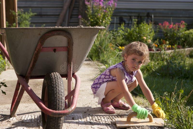 Mała biała dziewczyna betonuje ścieżkę w domu na wsi Lato, kwiatu łóżko w tle i wheelbarrow obok ch, obraz stock