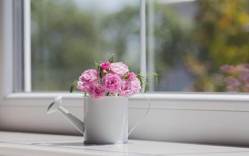 Mała biała podlewanie puszka z wiosną kwitnie bukiet blisko w zdjęcia royalty free