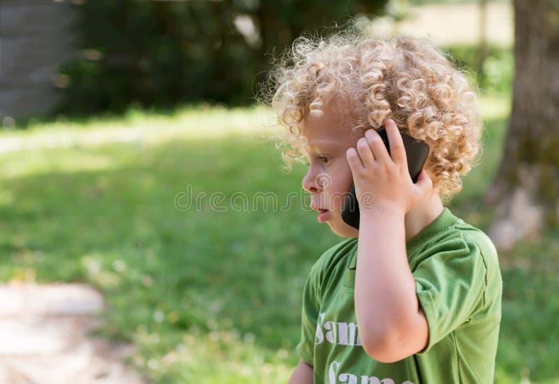 Mała blond chłopiec bawić się z telefonem komórkowym obrazy royalty free