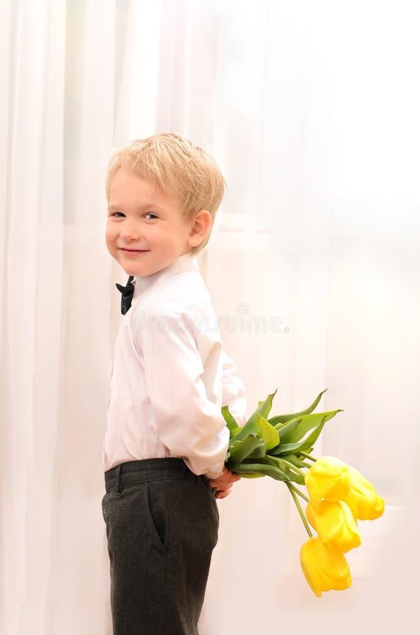 Mała blond chłopiec z bukietem kwiaty obraz royalty free