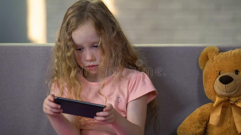 Mała blond dziewczyna bawić się grę na smartphone, gadżetu nałóg, dzieciństwo obraz royalty free