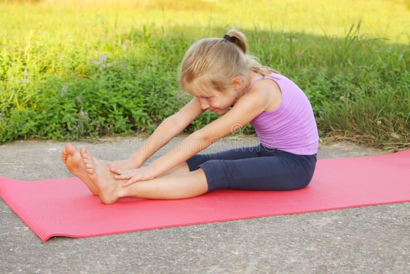 Mała blond dziewczyna robi sprawności fizycznej ćwiczy w parku i pić wodę obraz royalty free