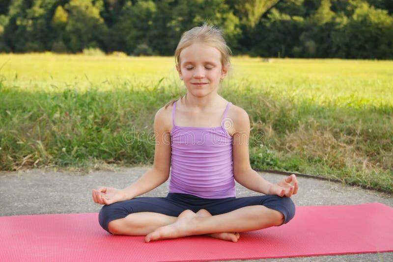 Mała blond dziewczyna robi sprawności fizycznych ćwiczeniom zaszaluje w parku fotografia royalty free