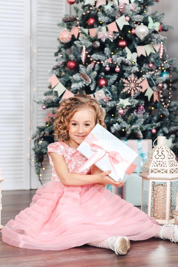 Mała blond dziewczyna siedzi pod choinki otwarcia prezentami z ślicznymi kędziorami zdjęcie royalty free