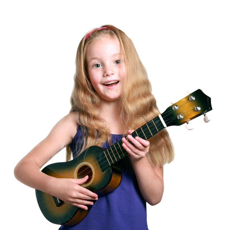 Mała blond dziewczyna w purpurach ubiera sztuka ukulele zdjęcie stock